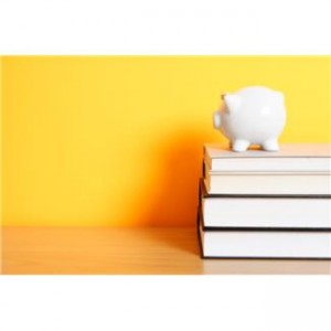 A Picture of a White Piggy Bank on top of a Stack of Books