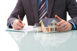 An image of a house and a man signing a contract